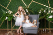 Little cute girls with blond hair in a white dresses holding a small dog and white flowers, lilies and orchids on a green background