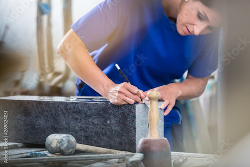 Craftswoman applying template for engraving on headstone Fototapete