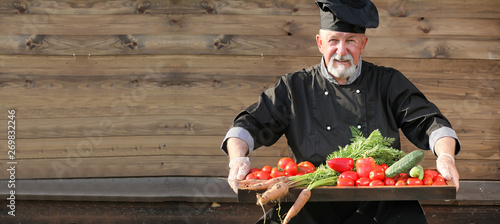 Chef old in uniform with vegetables Fototapet