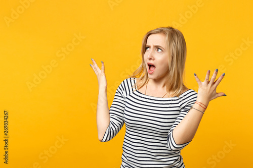 Fotografie, Tablou  Disgusted shocked young woman in striped clothes looking aside, spreading hands, screaming isolated on yellow orange wall background
