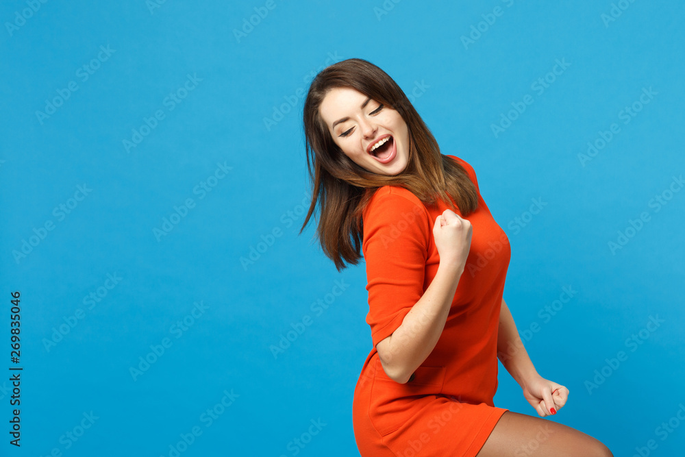 Fototapety, obrazy: Beautiful excited brunette young woman wearing red orange dress doing winner gesture, say Yes isolated over blue wall background, studio portrait. People lifestyle fashion concept. Mock up copy space.