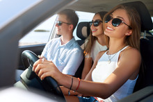 Group Of Friends Rented A Car On Summer Road Trip And Arrived To The Sea Beach. Girl Having Fun With Friends In Vehicle. Woman In Glasses Learned Driving And Got A Driver License. Travel Lifestyle.