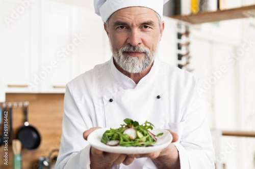 Fotografía  male cook chef decorating garnishing prepared salad dish on the plate in restaurant commercial kitchen