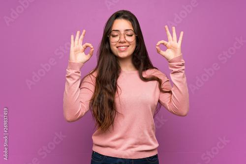 Teenager girl over purple wall in zen pose
