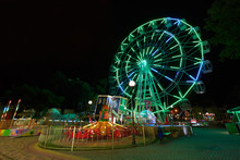 Amusement Park At Night With A Ferris Wheel And Carousels. Glowing Ferris Wheel