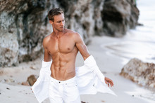 Sexy Muscular Man In A White Shirt With A Bare-chested Resting On The Beach, Ocean Waves At Background.