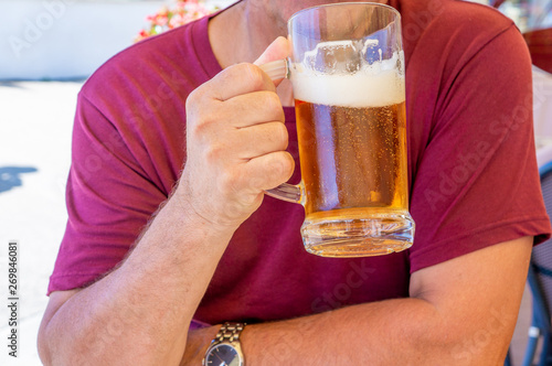 Canvas Prints Beer / Cider An unidentified man drinks out of a large glass mug of light beer on the background of a pub on a wooden table
