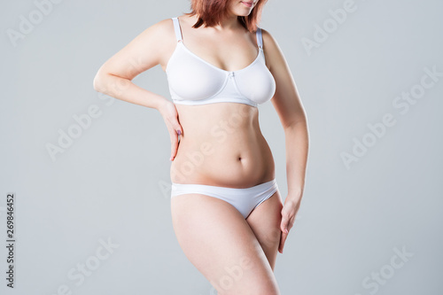 Fényképezés  Woman with fat flabby belly, overweight female body on gray background