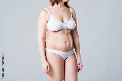 Woman with fat flabby belly, overweight female body on gray background Fototapeta
