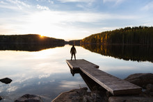 Lonely Man Standing On The Edge Of The Wooden Pier Looking At The Calm Lake And Colorful Forest On The Other Side