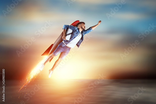 Fototapeta A man flies on a rocket, delivers parcels. Super fast delivery, cool service, online purchase. Copy space, Mixed media obraz