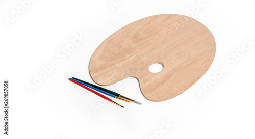 Wooden art palette with paint brush on white isolated