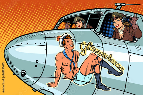 Foto women pilots girls. Pinup man on the fuselage of a retro bomber