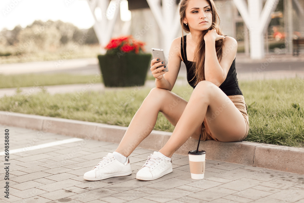 Fototapeta Beautiful young woman using phone and drink coffee sitting on the curb in the street.