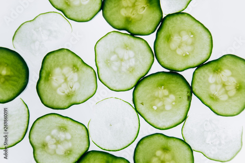 green translucent slices of cucumber on the background of bright white light close-up Canvas Print