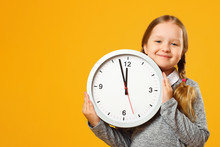 Little Girl With Pigtails Holds A Big Clock On A Yellow Background. The Concept Of Education, School, Timing, Time To Learn. Closeup Portrait. Copy Space.