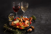 Paella On A Pan With Shrimp, Mussels And Wine On A Black Table. Spanish Mediterranean Cuisine. Seafood Is A Healthy Food Concept. Copy Space.