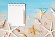 Notebook, starfishes and seashells on sand background top view. Planning summer holidays, trip, travel and vacation concept. Flat lay style.