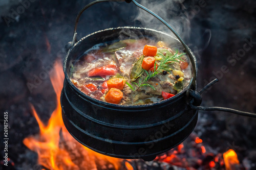 Photo  Tasty and spicy hunter's stew on bonfire