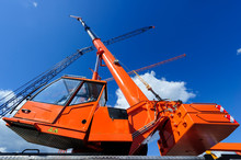 Mobile Construction Crane With Telescopic Arm Mounted On Truck With Orange Bodywork And Big Tower Cranes In Sunny Day With White Clouds And Deep Blue Sky On Background, Heavy Industry