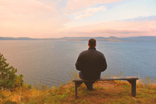 A Man Sits On A Bench And Looks At The Lake. Lake And Mountains. Background. Landscape.