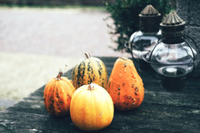 Authentic Decoration For Halloween, Outdoor Table With Small Pumpkins And Glass Lamps
