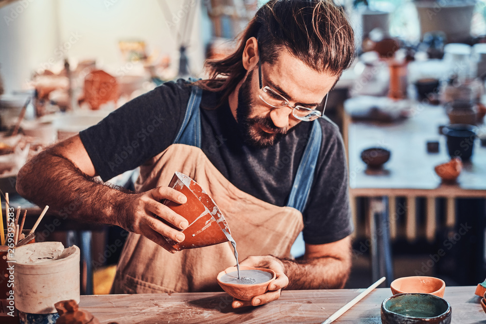 Fototapety, obrazy: Diligent man is putting colourful clay to his new handmade pot.