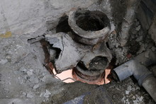 Garbage And Dirt During Sewage Repair. Hole Between The Floors Of An Apartment Building. A System Of Broken Sanitary Pipes In An Old House. The Concept Of Replacement Of Iron Pipes For Plastic.