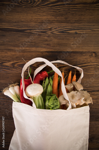 Fresh vegetables in bio eco cotton bags on old wooden table. Zero waste shopping concept. Plastic free. Lots of copy space.