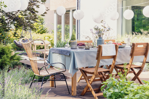 Foto  Table with wooden chairs in bright green garden of modern house, real photo