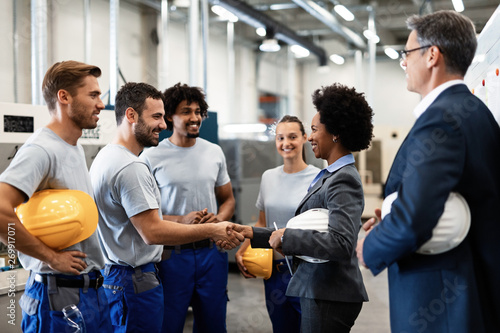 Photo  Happy African American businesswoman shaking hands with one of factory workers