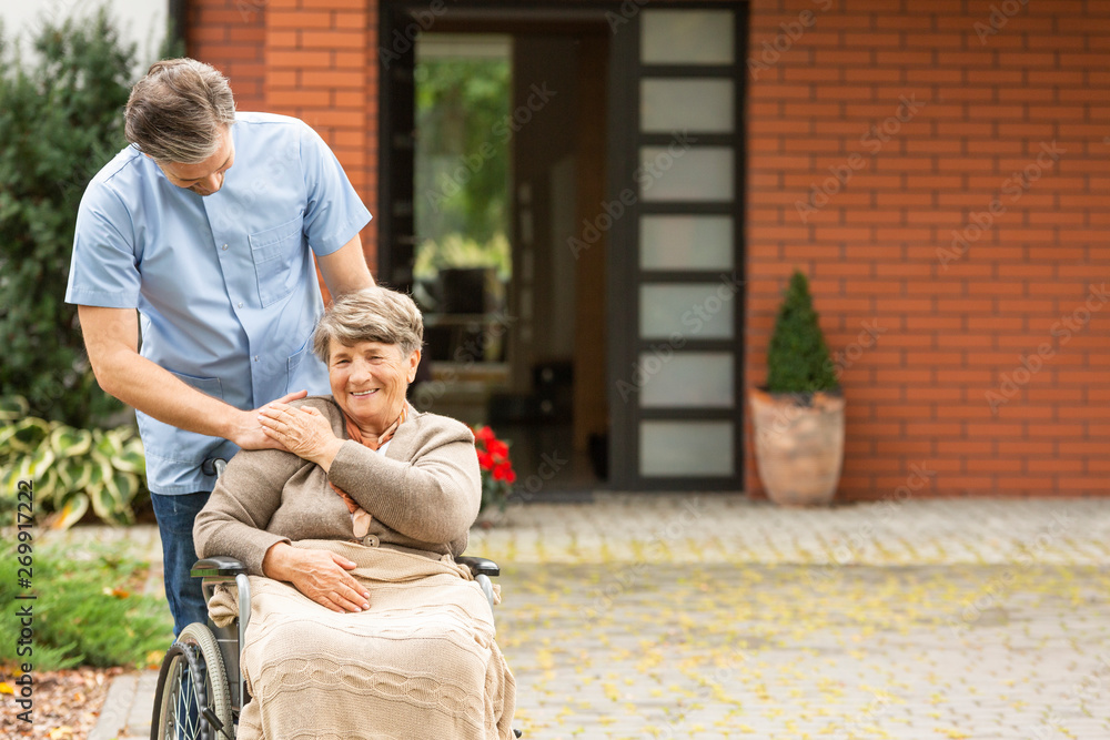 Fototapety, obrazy: Caregiver helping smiling disabled senior woman in the wheelchair in front of house