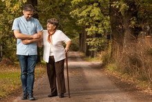 Male Nurse Supporting Happy Elderly Woman With Walking Stick In The Forest