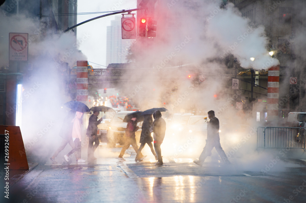 Fototapety, obrazy: Undefined people with umbrellas are crossing the 42nd street in Manhattan. Steam coming out from from the manholes in the background. Manhattan, New York City, Usa.