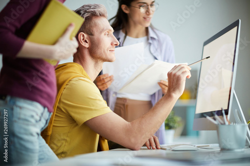 Side view portrait of contemporary business team using computer together, focus on man pointing at computer screen, copy space - 269927297