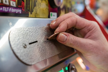 A Woman Plays A 2p Tuppeny Nudger Machine In A Funfair At A British Seaside Resort.