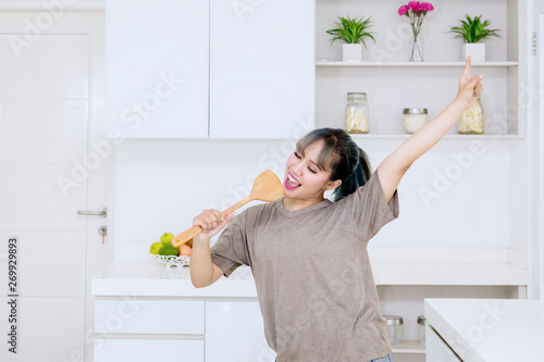 Fotografie, Obraz Happy young woman singing with a spatula