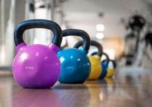 Colorful Kettlebells In A Row In A Gym, Purple, Blue, Yellow.