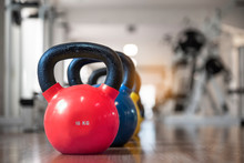 Colorful Kettlebells In A Row In A Gym, Red, Blue, Yellow.