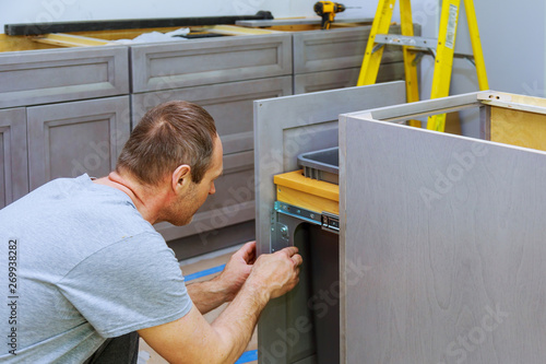 A carpenter is building a drawers garbage bin in the kitchen Fototapet