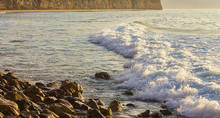 Pastel Colored Foam Rolling Infront Of Wave Towards Rocky Shore With Cliff And Sandy Beach
