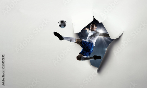 Photo  Paper breakthrough hole effect and soccer player. Mixed media