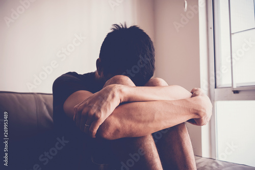 Fotografía Depressed and anxiety man sitting alone at home, mental illness health concept