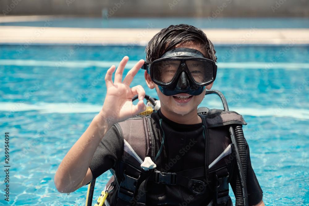 Fototapeta Young little Asian tween preteen boy scuba diver showing ok hand signal, diving lessons for beginners, teen travel,  Sign Language