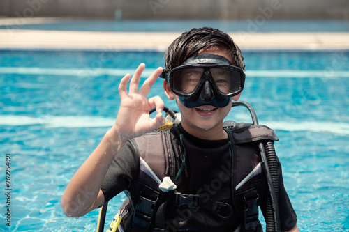 Fototapeta Young little Asian tween preteen boy scuba diver showing ok hand signal, diving lessons for beginners, teen travel,  Sign Language obraz