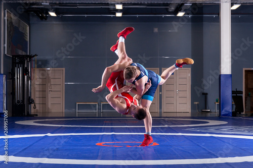 Fototapeta  Two strong wrestlers in blue and red wrestling tights are wrestlng and making a  making a hip throw  on a yellow wrestling carpet in the gym