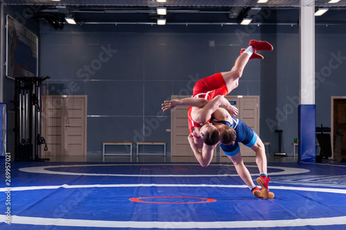 Obraz Two young men in blue and red wrestling tights are wrestlng and making a suplex wrestling on a yellow wrestling carpet in the gym. The concept of fair wrestling - fototapety do salonu