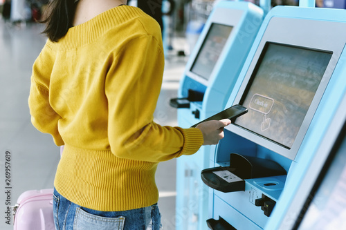 Fotografía Traveler using a self check-in machine kiosk service at airport, Technology and smart application to confirm flight booking details, Travel concept