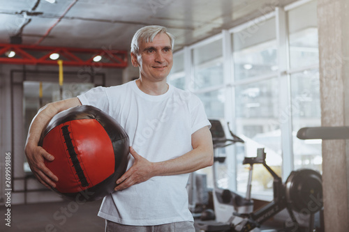 фотографія  Happy senior healthy man looking away joyfully, smiling, holding medicine ball