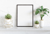 Black frame leaning on white shelve in bright interior with plants and decorations mockup 3D rendering - 269962874